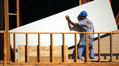 Worker moves a drywall to the higher floor at construction site - stock footage