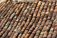 Stock Photo of old tiled red roof with moss showing weathered age