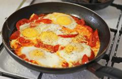 Fried eggs with tomato on the pan Stock Photos