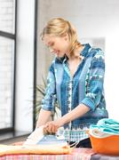 lovely housewife with iron - stock photo