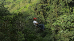 men passes over the camera on zip line - stock footage