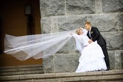 Bride and groom kissing near the wall Stock Photos