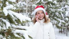 Cheerful woman talking on the phone in the bell santa claus Stock Footage