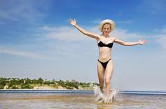 Happy girl runs in the water Stock Photos