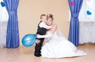 Stock Photo of the beautiful bride embraces her little brother
