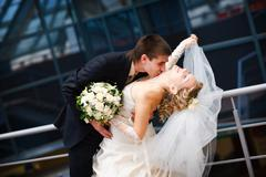 Groom and bride kiss under the glass ceiling Stock Photos