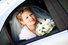 happy bride with flower bouquet siting in the car - stock photo
