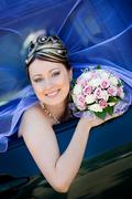 happy bride with flower bouquet sitting in the car - stock photo