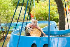 Child in the boat in the amusement park Stock Photos