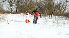 Father and daughter running in the snow Stock Footage