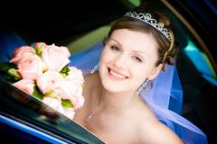 Happy bride with flower bouquet siting in the car Stock Photos