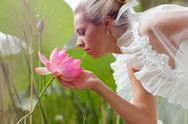 Stock Photo of happy bride smelling a lotus flower