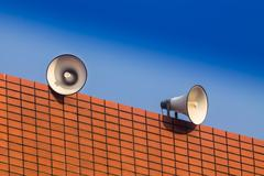 loudspeakers on builing and blue sky background - stock photo
