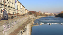 Teenager sat next to River Po in Torino Stock Footage
