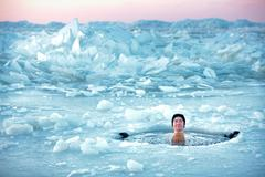 Winter swimming. Man in an ice-hole Stock Photos