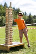 Cute little boy with wooden tower game Stock Photos