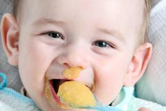 Stock Photo of Laughter baby boy eating vegetable mash