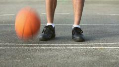 Basketball player bouncing the ball whilst standing Stock Footage
