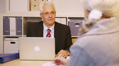Consultant talking to elderly customer in office Stock Footage
