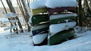 Stock Video Footage of eight boats turned upside down are covered with snow