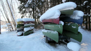 Two sets of boats piled upside down with snow Stock Footage