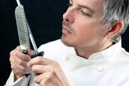 Stock Photo of chef sharpens knife