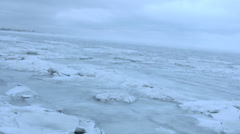 Panning right to a lonely figure on an endless icy field in the Arctic - stock footage
