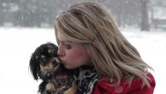 Blonde girl kisses puppy in Snowstorm Stock Footage