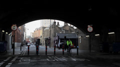LONDON - Man with hoodie speaks over the phone under a bridge Stock Footage