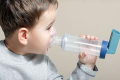 Close-up image little boy using inhaler for asthma. Stock Photos