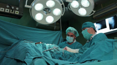 Surgeons team performing operation in hospital operating room, surgeon close up Stock Footage