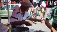 Stock Video Footage of An Old Asian Ice Cream Seller Scooping Ice Cream In Sunny Day
