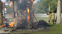Amid the Force of Nature - House fire wall pushed by firemen Stock Footage