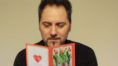 Man reads a Valentine's Day card Stock Footage