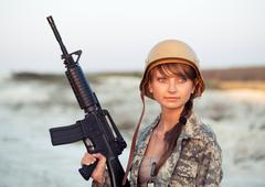 young female soldier dressed in a camouflage with a gun in the outdoor - stock photo