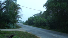 A Car Passing By On Cornering Road In Malaysian village Stock Footage