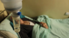 Old man, patient lying down on bed in hospital rum. Infusion close up.;;; - stock footage