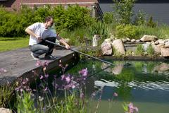 Man cleanse his garden pond Stock Photos