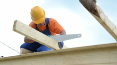 Carpenter works with hand saw Stock Footage