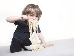 Child eating spaghetti joyfully Stock Photos