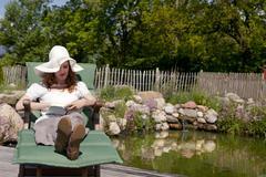 Woman enjoys garden pond lies, frau geniesst gartenliege teich Stock Photos