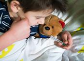 Stock Photo of sick child in bed with teddy bear