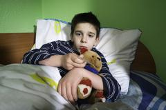 sick child in bed with teddy bear - stock photo