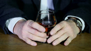 Stock Video Footage of Glass of cognac, brandy, in hands  businessman