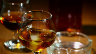 Stock Video Footage of Ice falls in a glass with cognac, whisky close up