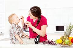 mother feeding child with grapes - stock photo