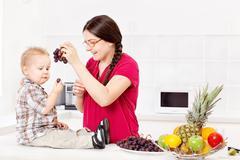 mother feeding child in kitchen - stock photo