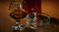 Ice falls in a glass with cognac, whisky Footage