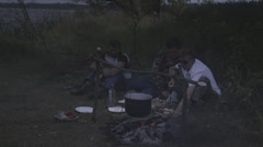 Men cook over a campfire Stock Footage