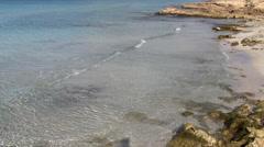 Placid sea, beach and rocks - stock footage